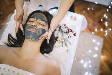 Anwenden der Gesichtsmaske auf das Gesicht der Frau im Schönheitssalon