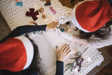 Manicurist with Santa hat doing Christmas manicure Imagens