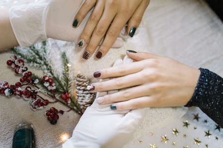 Girl showing her Christmas manicure at nail salon