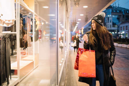 Girl standing in front of the shop window and looking at clothes