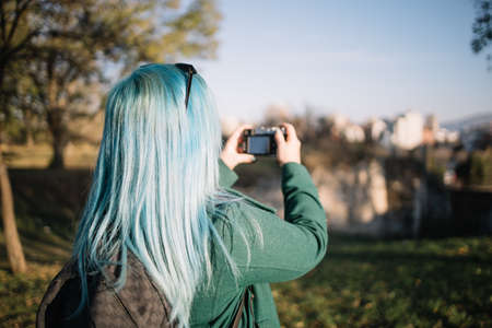 Back of a girl with blue hair shooting city view Banco de Imagens - 138282436