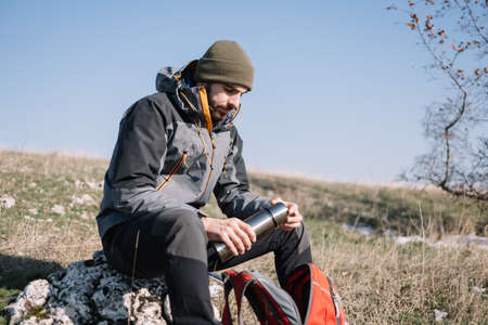 Bearded hiker resting on a stone and holding thermos Stock Photo