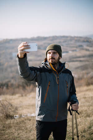 Tourist man taking photo of himself with smartphone