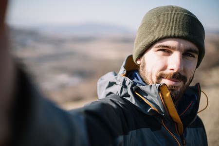 Selfie of a bearded male tourist in nature