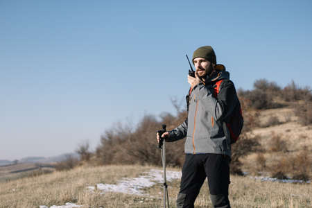 Young hiker man speaking on mountain walkie-talkie