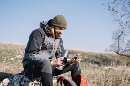 Male hiker sitting on a rock and opening thermos