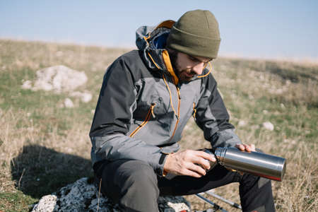 Traveler man pouring hot tea and sitting on the mountain rock 版權商用圖片