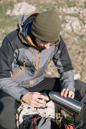 Hiker man sitting on a rock and pouring coffee from thermos 版權商用圖片
