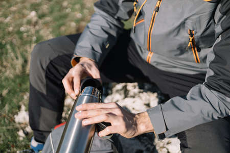 High angle view of hiker man pouring coffee from thermos