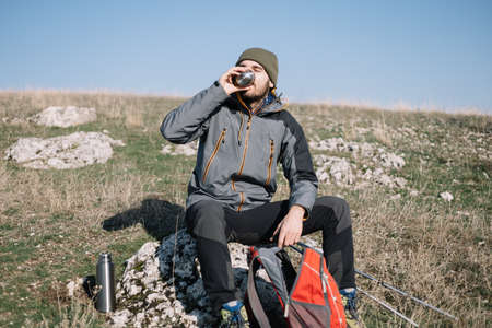 Male hiker sitting on a rock and drinking coffee