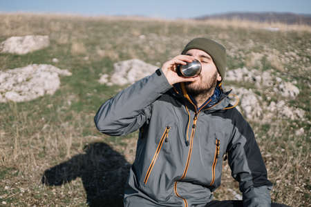 Tourist man drinking tea on a field with mountain view 版權商用圖片