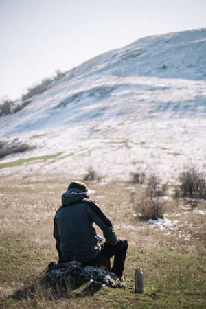Back of a man sitting on a rock with snow mountain Stock Photo