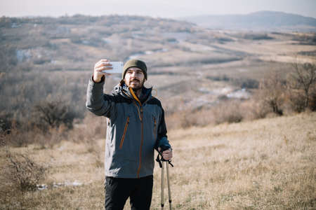Male hiker making selfie while standing on a field