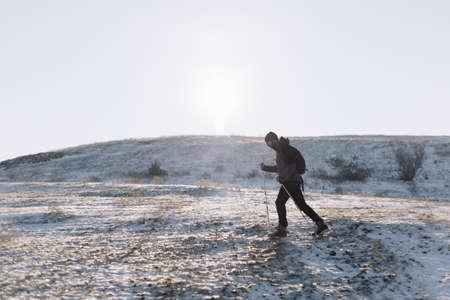 Hiker man walking on a snow mountain