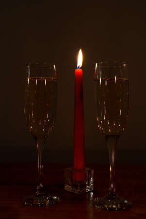 Burning red candle and two champagne glasses