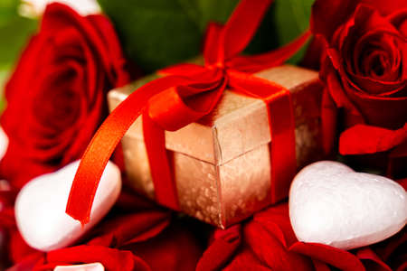 Golden gift box with red ribbon between red roses. Close-up of wrapped gift box for Valentines day with red roses and hearts. Foto de archivo