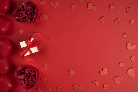 Present for Valentine's day with heart shaped confetti. Gift box and heart shaped boxes with roses surrounded with red hearts, top view.