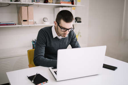 Office worker with glasses using laptop on desk