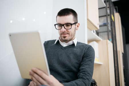 Employé concentré à la recherche d'une tablette Banque d'images