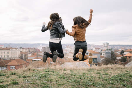 Backview of two girls in the air with hands clasped. Brunette women jumping in the air and holding hands with city view.