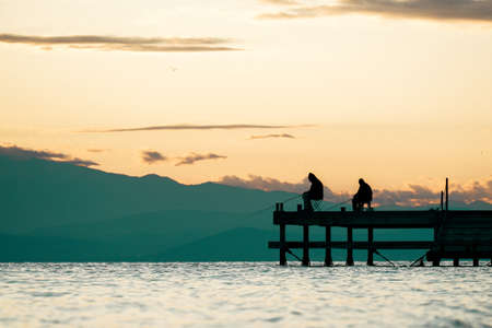 Silhouettes of two fishermen sitting on a dock during sunset. Men fishing while sitting on pier with fishing rods and waiting to catch fish.