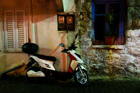 Night photo of scooter leaning on wall