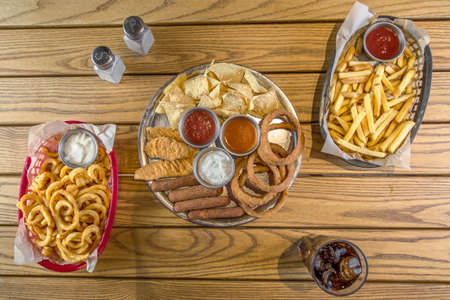 Top view of assorted snacks on wooden table. Wooden table with coke, salt and pepper, fried onion rings, fish fingers, breaded squid, chips, potatoes, sauces and tortilla.