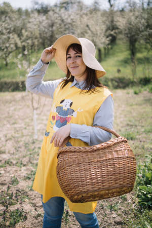 Girl with sun hat and basket standing on field