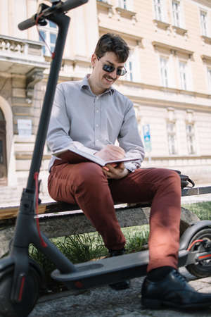 Smiling man in elegant outfit sitting on bench near electric scooter