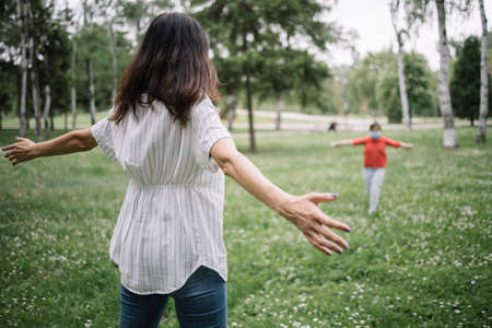 Back view of mother with opened arms waiting her child for a hug. Back of woman with spread hands looking at running little girl in park.