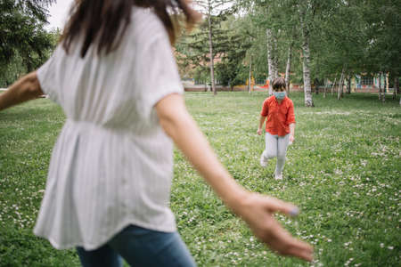 Mother waiting to hug her child with medical mask in park. Back view of blurred woman with opened arms standing in park towards her child protected against coronavirus.