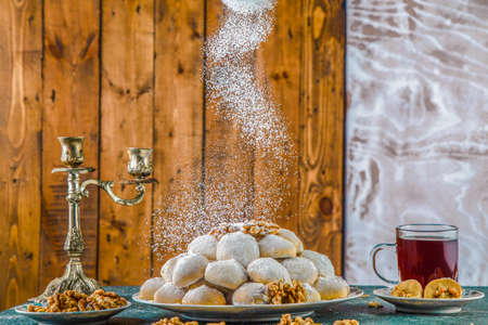Sprinkling powdered sugar over cookies against wooden background. Sprinkling sugar powder over biscuits and walnuts arranged in plate on table with cup of tea and antique candlestick holder.