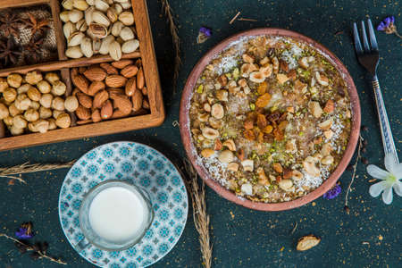 Umm Ali on table with nuts and milk. Oriental dessert with Egyptian bread and chopped nuts on table next to cup of milk and box with almonds, star anise, hazelnuts and pistachio.