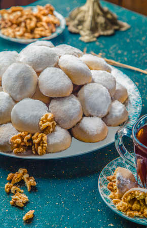 Close-up view of biscuits covered with powdered sugar. Butter cookies with powdered sugar and walnuts on blue table with tea and walnuts.