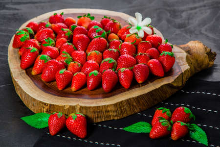 Strawberries arranged on wooden board with flower. Mellow strawberries on wooden slice on table runner with dark wooden background.