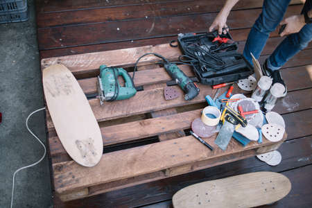 Tools for making skateboard on pallet in workshop. Top view of wooden pallet with handyman tools and skateboard parts. Imagens