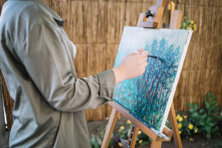 Cropped woman painting picture on canvas outdoor. Female hand holding paintbrush and painting on canvas on wooden tripod in garden with flowers. 免版税图像