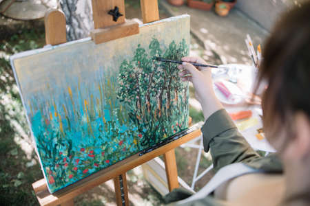 High angle view of cropped woman painting in yard. Hand with paintbrush painting picture on canvas in backyard with paint tubes and brushes. 免版税图像