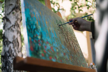 Close-up view of cropped woman holding paintbrush and painting. Female hand holding brush over painted canvas on tripod in nature in front of tree. 免版税图像