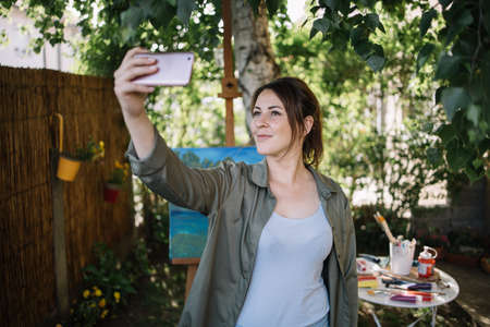 Beautiful woman taking selfie in outdoor studio. Female artist taking photo of herself using phone while standing in garden.