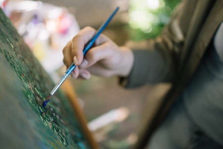 Womans hand holding brush and painting picture. Cropped woman hand painting picture on canvas using brush outdoor.