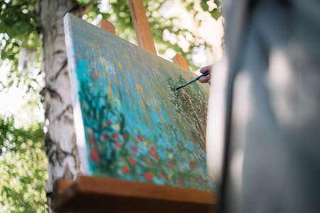 Female hand holding brush over painted canvas on tripod in nature. Close-up view of cropped woman holding paintbrush and painting picture outdoor.