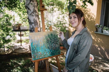 Happy woman with paint brush posing in front of painted canvas. Beautiful female artist holding used paint brush and standing in front of painting outdoor while looking at camera.