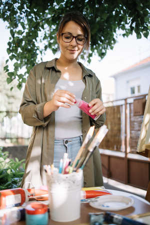 Girl holding paint tube in outdoor workshop. Woman artist wearing eyeglasses and standing in outdoor studio with canvas stand and painting accessories. 免版税图像