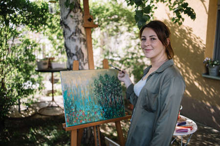Beautiful female artist holding paint brush in front of painting. Young woman holding paint brush and looking at camera while standing in outdoor atelier. 免版税图像