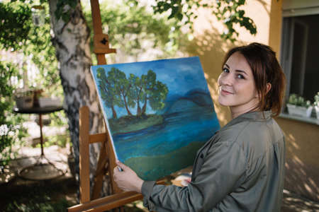 Young woman holding painting while standing near tripod. Portrait of female artist posing while holding painting and looking at camera in yard.