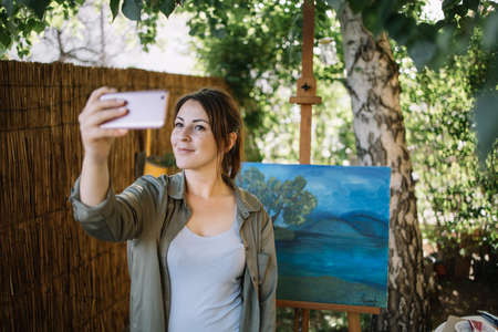 Pretty girl posing in front of painted canvas and taking selfie. Woman taking selfie while standing in front of painting in outdoor atelier.
