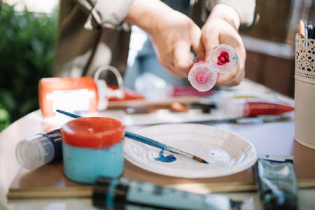 Female hands squeezing red aquarelle paint tube. Close-up of cropped woman pressing paint tube over plastic plate on table with brushes and paint tubes.