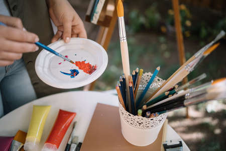 Cropped artist mixing paints in outdoor studio. Close-up view of female artist hands mixing paints in plate over table with brushes, pencils and paint tubes.