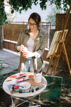 Beautiful female artist standing in outdoor studio. Pretty woman wearing glasses holding paint tube over table with paint brushes and paint tubes.